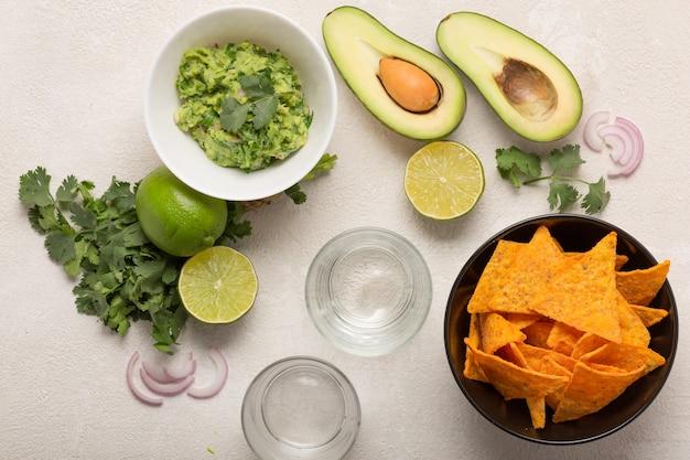 Guacamole, chipsy kukurydziane i piwo, lekka meksykańska przekąska lub kolacja, widok z góry