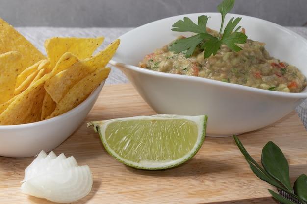 Guacamole i nachosy w białych miseczkach. meksykańskie jedzenie.