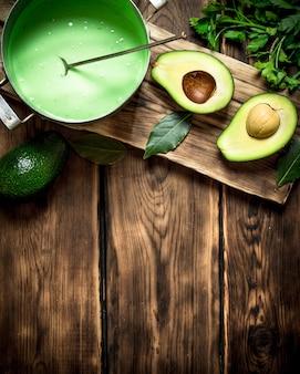 Guacamole i zielenie na pokładzie. na drewnianym tle.