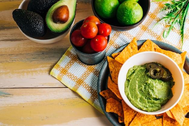 Guacamole miska z nachos na vintage drewnianym stole ze świeżymi składnikami wokół niego. skopiuj miejsce wegańskie jedzenie
