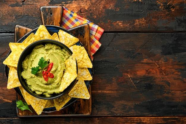 Guacamole. tradycyjny latynoamerykański sos meksykański w czarnej misce z awokado i dodatkami oraz kukurydzianymi nachos
