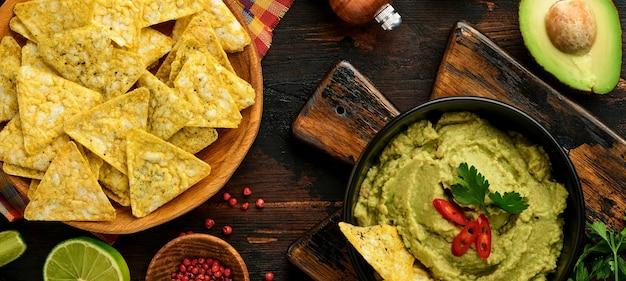 Guacamole. tradycyjny latynoamerykański sos meksykański w czarnej misce z awokado i dodatkami oraz kukurydzianymi nachosami. pasta z awokado. widok z góry. copyspace