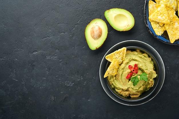 Guacamole. tradycyjny latynoamerykański sos meksykański w czarnej misce z awokado i dodatkami oraz kukurydzianymi nachosami. pasta z awokado. widok z góry. miejsce.