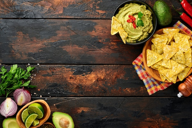 Guacamole. tradycyjny latynoamerykański sos meksykański w czarnej misce z awokado i dodatkami oraz kukurydzianymi nachosami. pasta z awokado. widok z góry. skopiuj miejsce.