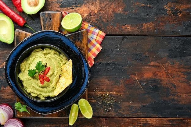 Guacamole. tradycyjny latynoamerykański sos meksykański w czarnej misce z awokado i dodatkami