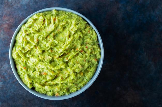 Guacamole w szarej misce na ciemnym tle. miska sosu guacamole z awokado ze świeżymi składnikami. skopiuj miejsce. widok z góry