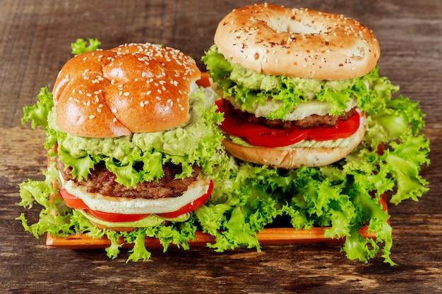 Guacamole wołowiny hamburger z rozciekłym serem na drewnianym tle
