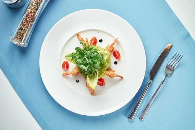 Guacamole z awokado z krewetkami, rukolą i pomidorkami koktajlowymi w białym talerzu na niebieskim obrusie. ścieśniać. meksykańskie jedzenie