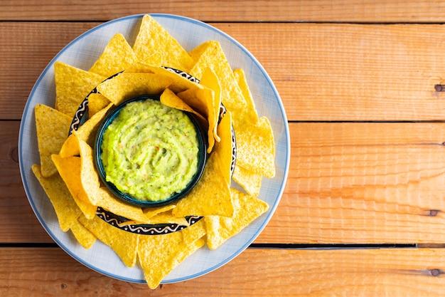 Guacamole z chipsami tortilla na drewnianych deskach. chipsy nachos i meksykański sos guacamole na talerzu. skopiuj miejsce. widok z góry