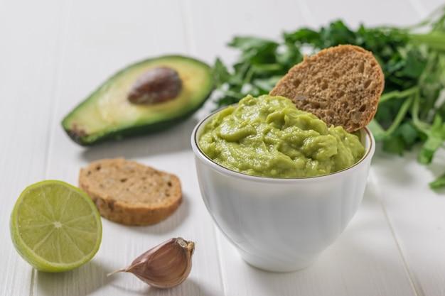 Guacamole z chlebem, limonką, czosnkiem i pietruszką na białym drewnianym stole. dieta wegetariańska meksykańskie jedzenie awokado. surowe jedzenie.