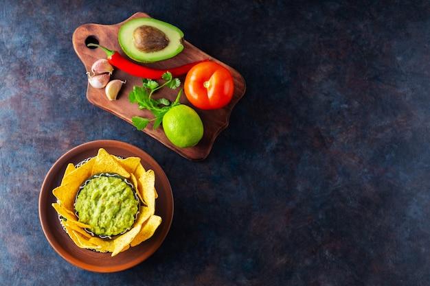 Guacamole z dodatkami i chipsami tortilla nachos. guacamole z awokado z dodatkiem pieprzu, limonki i nachosów kukurydzianych na ciemnym tle. skopiuj miejsce. widok z góry