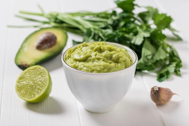 Guacamole z limonką i pikantnymi ziołami. dieta wegetariańska meksykańskie jedzenie awokado. surowe jedzenie.
