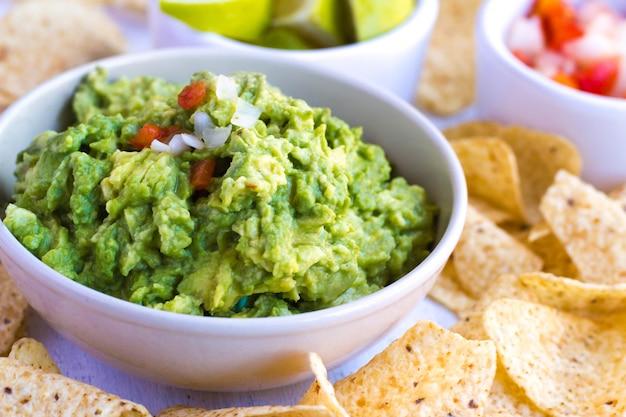 Guacamole z pico de gallo (cebula, kolendra lub chili i pomidor). wyśmienicie zdrowy avocado karmowy pojęcie na zakończenie widoku ,.