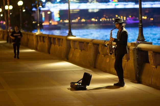 Guangzhou chiny, marzec, - 15, 2016: mężczyzna bawić się saksofon na ulicie w wieczór