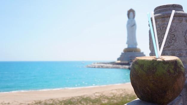 Guanyin z nanshan, biały posąg bodhisattwy guanyi w pobliżu świątyni nanshan w sanya, chiny. na pierwszym planie koktajl kokosowy, morze