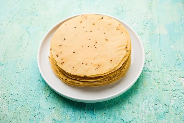 Gujarati papad lub papadum w postaci surowej suszonej z pieczonym rożkiem, bułką i odmianą płaską