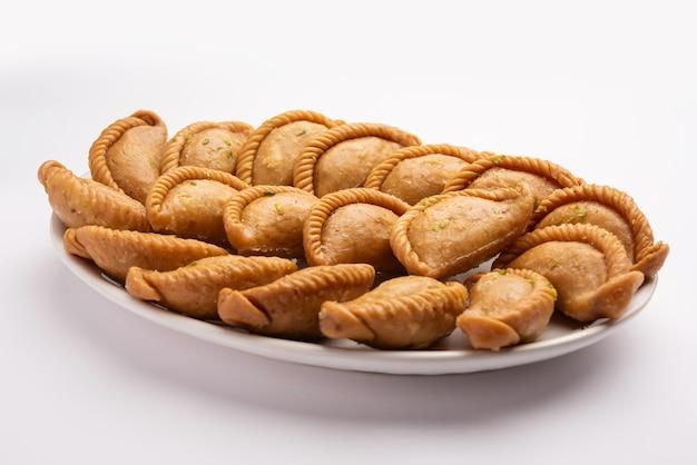 Gujiya lub gujia lub karanji. słodkie pierogi z okazji święta holi i diwali podawane na talerzu