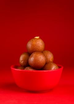 Gulab jamun w czerwonej misce. indyjski deser lub słodkie danie.