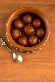 Gulab jamun w glinianym garnku z łyżeczką i suszonymi owocami. indyjski deser lub słodkie danie