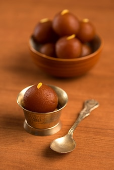 Gulab jamun w misce i miedziana antyczna miska z łyżeczką. indyjski deser lub słodkie danie.