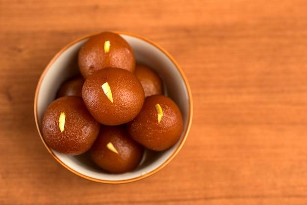 Gulab jamun w misce na drewnianym. indyjski deser lub słodkie danie.