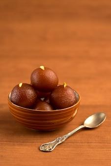Gulab jamun w misce na drewnianym stole. indyjski deser lub słodkie danie.