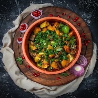 Gulasz mięsny w talerzu z ziemniakami, pieprzem, ziołami, cebulą, granatem