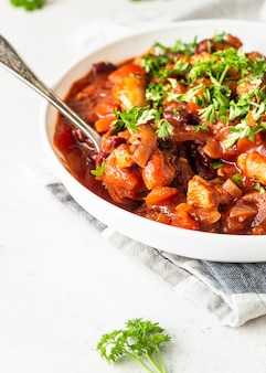 Gulasz mięsny z czerwoną fasolą, papryką i cebulą w sosie pomidorowym na białym talerzu na jasnoszarym łupku