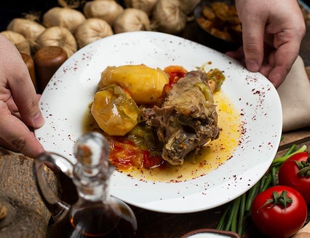 Gulasz mięsny z ziemniakami i tłustym bulionem na białym talerzu.