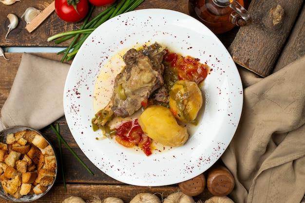Gulasz mięsny z ziemniakami, olejem i przyprawami. widok z góry.
