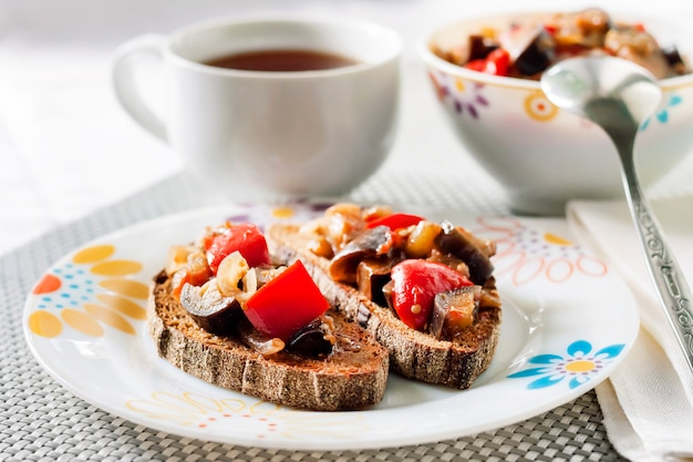 Gulasz warzywny z bakłażanem, czerwoną papryką i pomidorami na prażonym chlebie żytnim