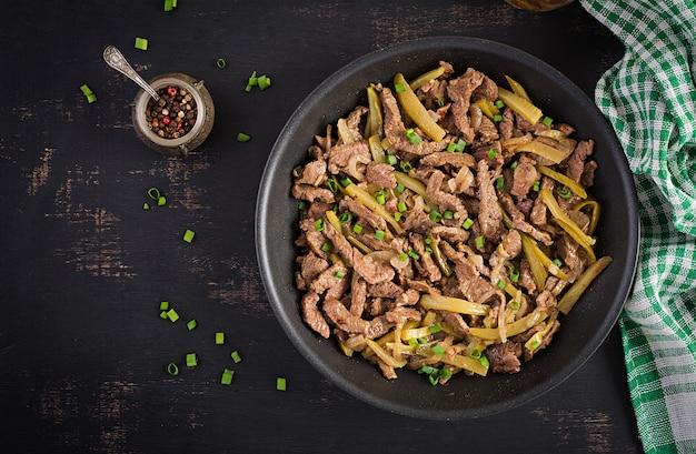 Gulasz wołowy, kawałki wołowiny duszone w sosie sojowym z przyprawami z kiszonym ogórkiem w stylu azjatyckim. widok z góry, z góry, płaski układ