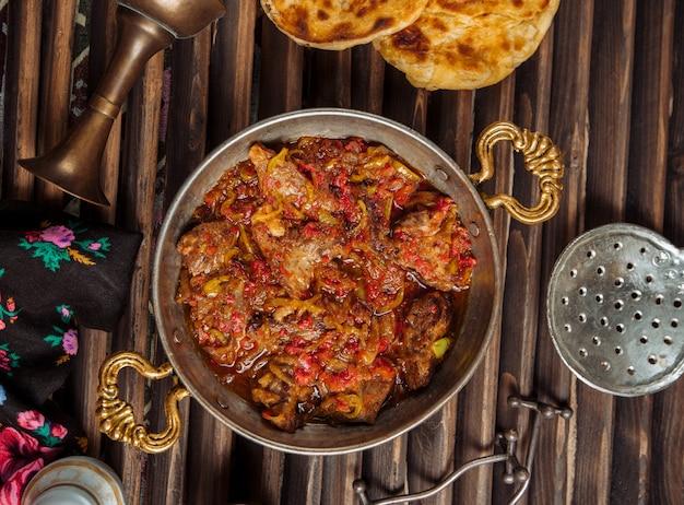 Gulasz wołowy w sosie pomidorowym w miedzianej patelni.