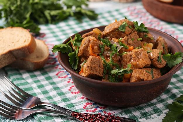 Gulasz wołowy znajduje się w brązowej misce na stole