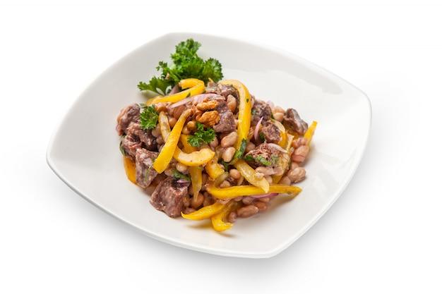 Gulasz z białej fasoli i dzwonkowego żółtego pieprzu z wołowiny mięsnym zbliżeniem z składnikami. na białym talerzu, na białym tle
