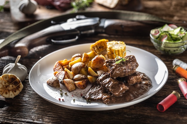 Gulasz z dziczyzny podawany z pieczonymi ziemniakami i doprawiony czterokolorową kukurydzą. całe jedzenie jest otoczone kulami myśliwskimi i strzelbowymi.