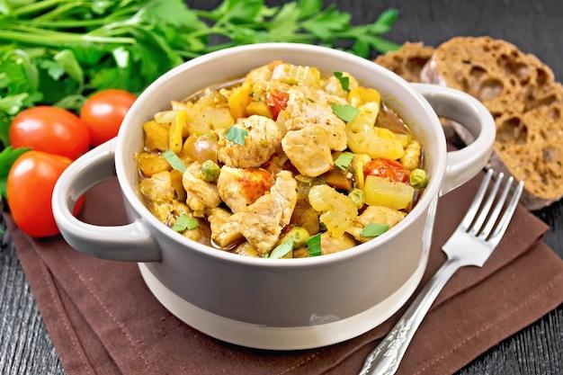 Gulasz z piersi kurczaka, pomidorów, selera naciowego, marchwi, zielonego groszku i cebuli w wazie na serwetce na tle drewnianej deski
