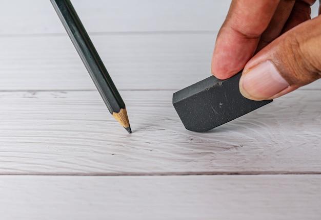 Gumka i błąd, ręka z czarną gumką i ołówkiem na białym stole