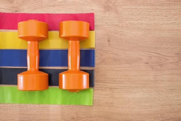 Gumki fitness i hantle na drewnianej powierzchni.