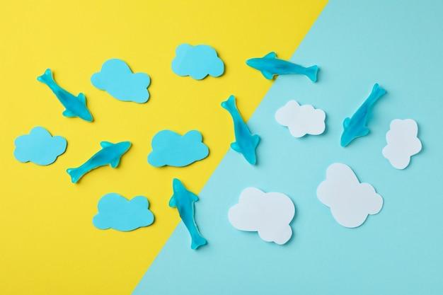 Gummy cukierki w postaci wieloryba i ozdobne chmurki na dwukolorowym tle.