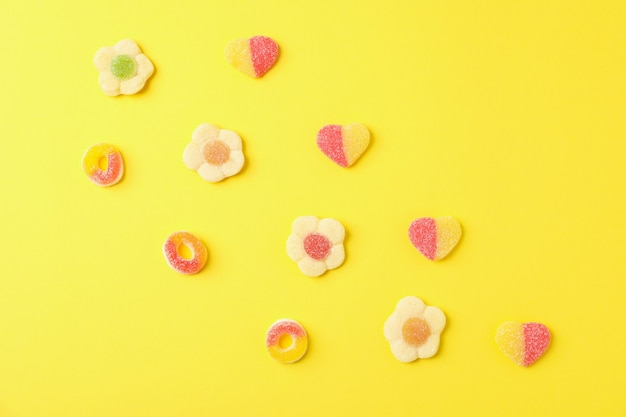 Gumowate cukierki na żółtym tle, widok z góry.