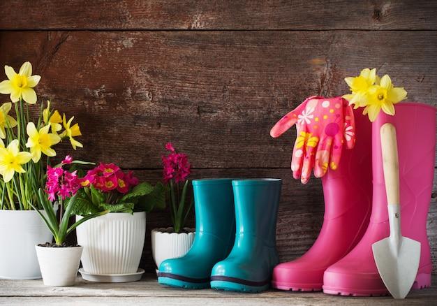 Gumowe buty i wiosenne kwiaty na drewnianej ścianie