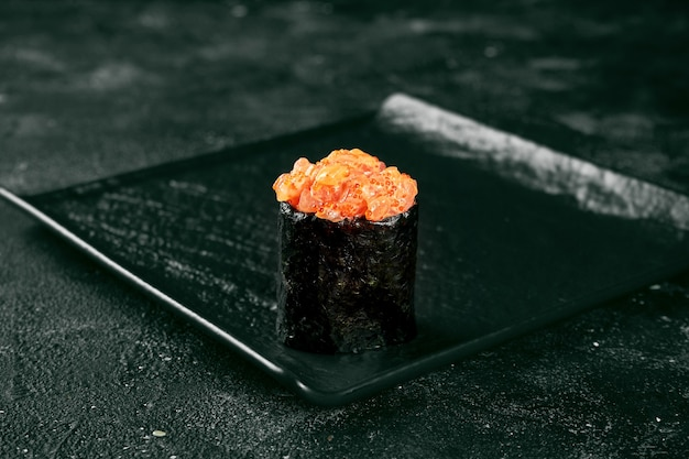 Gunkan maki sushi z łososiem i pikantnym sosem na czarnej desce. kuchnia japońska. dostawa jedzenia