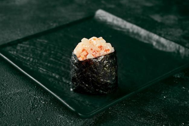 Gunkan maki sushi z łososiem i pikantnym sosem na czarnej desce z imbirem i wasabi. kuchnia japońska. dostawa jedzenia. czarne tło
