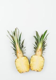 Gustowny ananas pokrojony na pół na białym. widok z góry.