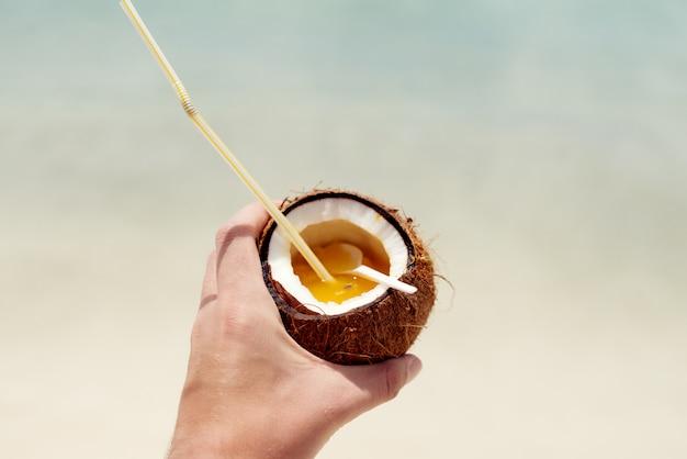 Gustowny koktajl pinnacolada w naturalnym kokosie z pięknym turkusowym oceanem
