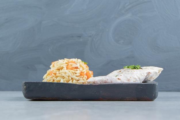 Gutabs obok ryżu na desce, na marmurowym tle.