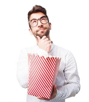 Guy with popcorn myślenia o filmie