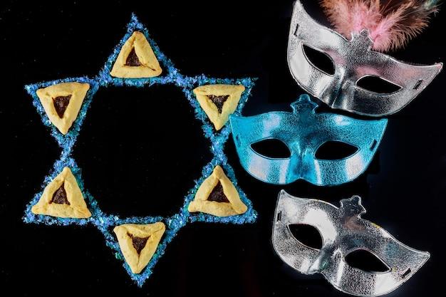 Gwiazda dawida z maską i ciasteczkami. symbol żydowski