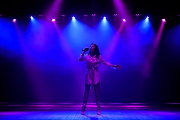 Gwiazda piosenkarki występująca solo na scenie w hali muzycznej w neonów